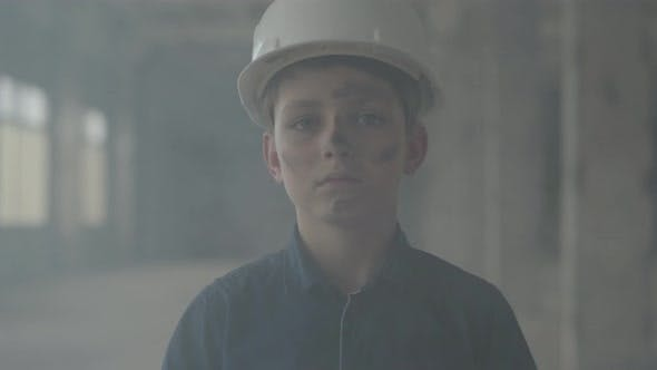 Thumbnail for Portrait Cute Boy in a Protective Helmet Looking at the Camera in the Background of Smoke Indoors