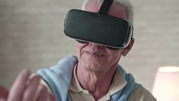 Thumbnail for Old Man in VR Goggles Touching Something in Air