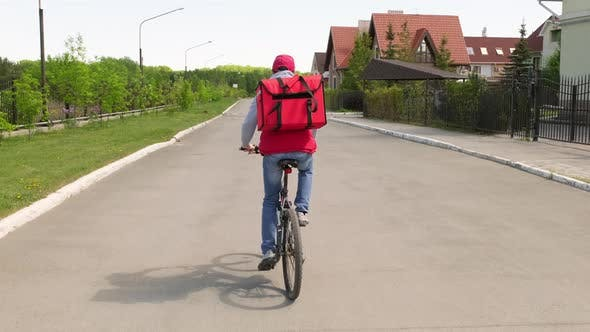 Thumbnail for Rear View of Delivery Man Riding Bike along Street