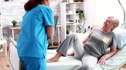 Female Nurse in Nursing Home Covering Old Woman with Blanket