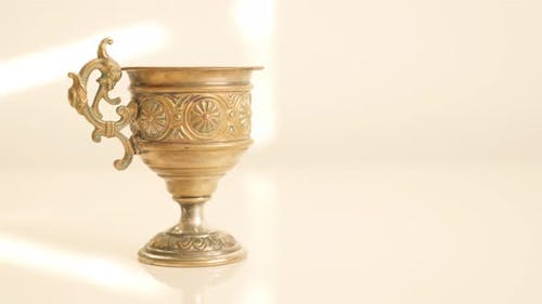 Made of  brass grail on white surface high detailed object 4K 2160p UltraHD tilt  footage - Lot of d