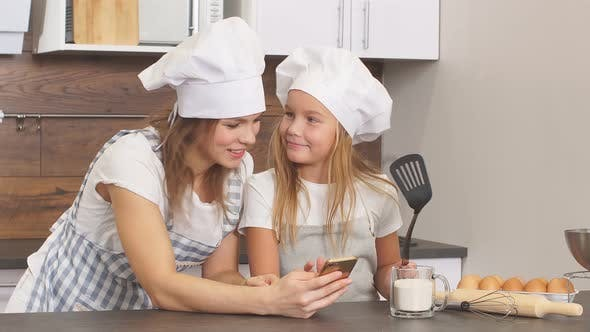Schöne Frau und Kind, die zu Hause leckere leckere Kuchen backen.