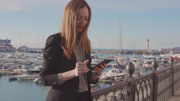 Thumbnail for Businesswoman Is Sending Messages By Mobile Standing on Terrace with Port View