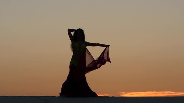 Cover Image for Girl Gracefully Dances with a Veil of Hands Against a Sunset. Silhouette