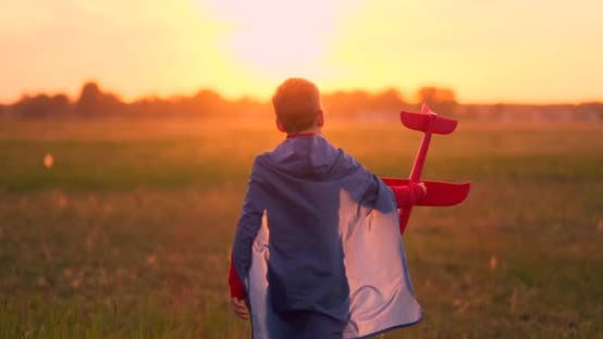 The Boy Presents Himself As a Pilot and Runs Into the Field at Sunset with a Plane