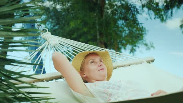 Thumbnail for A Young Woman Is Resting in a Seaside Resort in a Hammock, Enjoying a Vacation