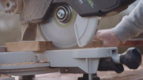 Zimmermann mit Gehrungssäge zum Schneiden von Holz