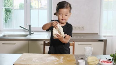 Little Girl Stretching Dough on Wooden Board in Kitchen