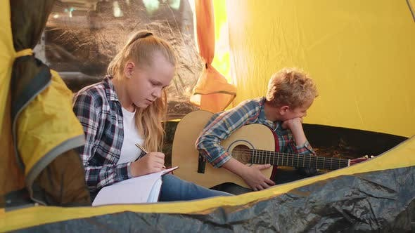Thumbnail for Teenager Girl and Boy with Guitar Sitting Inside Camping Tent in Forest. Girl Teenager Thinking