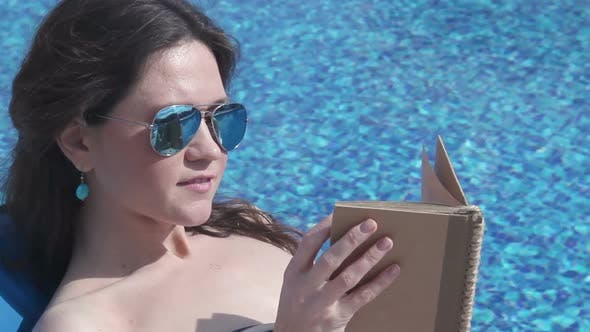 Thumbnail for Beautiful Woman Relaxing With Book by Pool, Sunbathing at Beach
