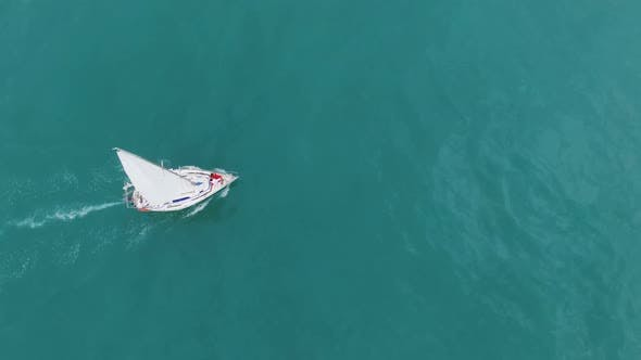 Thumbnail for Male female standing at bow of luxurious sailing boat going across turquoise sea