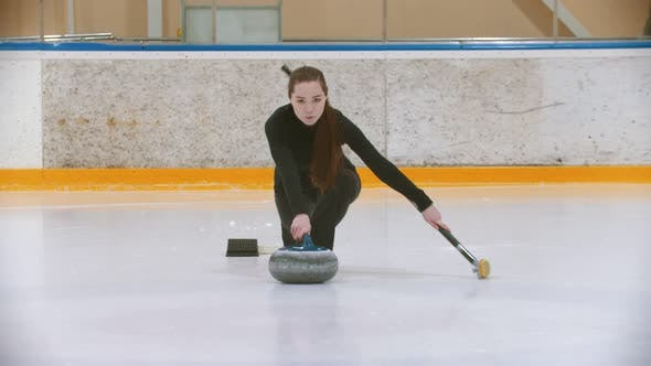 Thumbnail for Curling Training - a Young Woman with Long Hair Pushes Off From the Stand - Leading the Stone Biter
