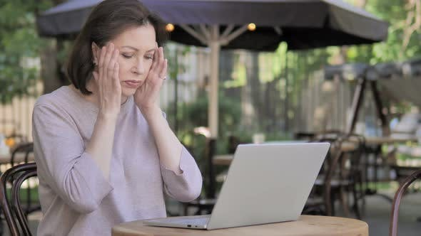 Thumbnail for Old Woman with Headache Using Laptop, Sitting Outdoor