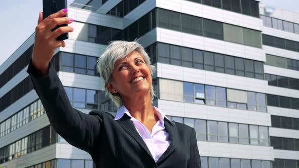 Thumbnail for Business Middle Age Woman Takes Selfies with Smartphone - Company Building in the Background
