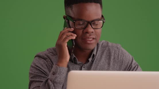 Thumbnail for Black male with glasses talks on the phone working on his laptop on green screen