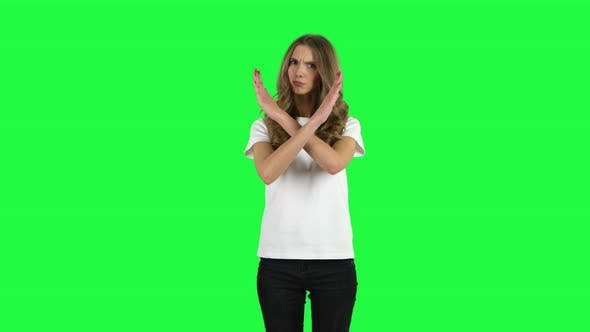 Cover Image for Lovable Girl Strictly Gesturing with Hands Crossed Making X Shape Meaning Denial Saying NO. Green