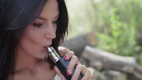 Portrait of Female Smoking Ecigarette and Exhales at Camera on Summer Nature