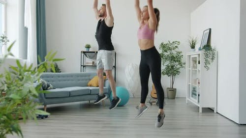 Man and Woman Doing High Intensity Interval Training Exercising Together at Home