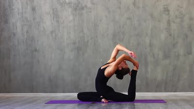 Woman Sports Clothes is Engaged in Yoga on a Purple Sports Mat Studio with Natural Consecration