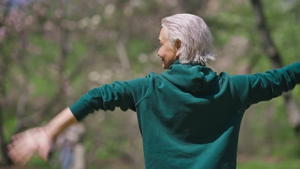 Back View of Senior Greyhaired Woman Stretching Hands Behind Back