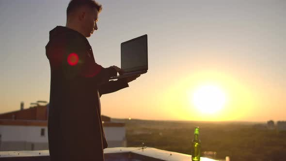 Thumbnail for A Male Stockbroker Freelancer Stands on a Rooftop at Sunset with a Laptop and Types on a Keyboard
