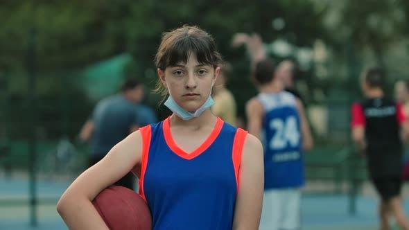 Ein Mädchen Basketballspieler mit einem Ball schaut auf die Kamera und setzt eine medizinische Maske auf. Outdoor-Sport