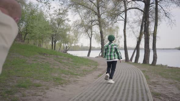 Thumbnail for Little Boy Running From His Grandfather in the Park