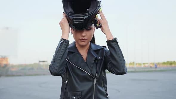 Thumbnail for Female Biker Putting on Black Helmet, Sitting on Black Motorbike and Looking at Camera
