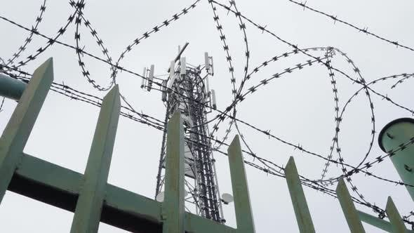 Thumbnail for A View From Below of a Telecommunication Tower, Through a Sharp Wire Fence.
