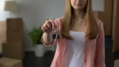 Woman Showing Key From Apartment, Affordable Lending, Investment in Real Estate