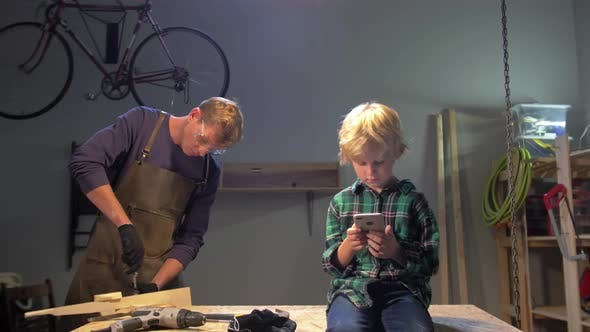 Thumbnail for Boy Sits with Phone, Man Works in a Workshop