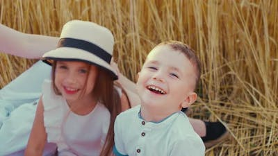 Little Boy Laughing in Field at Family Picnic