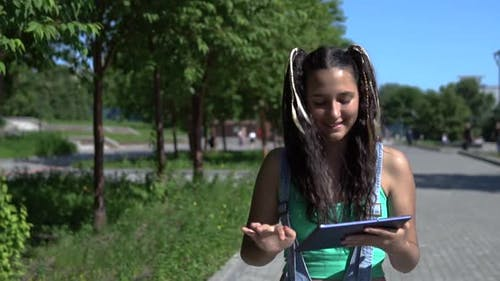 Attractive Girl Walks in the Park Using a Tablet