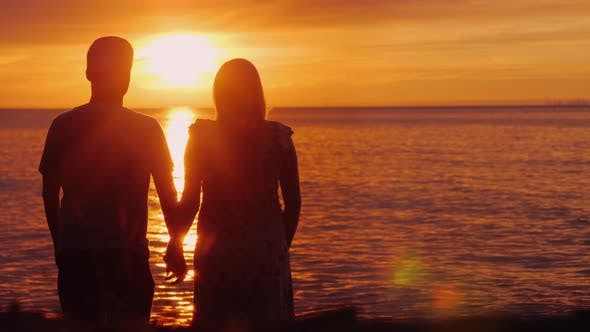 Thumbnail for Romantic Multi-ethnic Couple Admires the Scenic Sunset Over the Sea. Holding Hands, Rear View