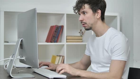 Shocked Creative Man Wondering and Working on Desktop