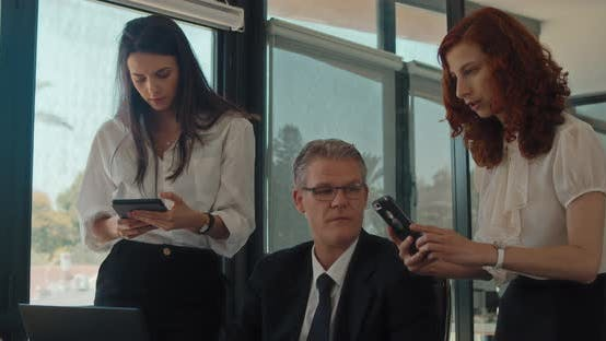 Thumbnail for A young businesswoman taking a picture of something from a computer during a business meeting