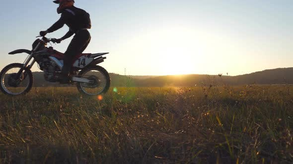 Thumbnail for Two Motorcyclists Passing Through Field with Beautiful Sunset at Background. Warm Summer Sun Lights