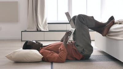 Lazy AfricanAmerican Man Works on Laptop Lying on Floor