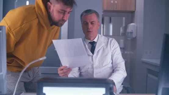Middle Aged Doctor Consulting Adult Patient in MRI Lab