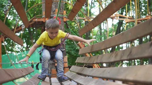 Close-up of a Small Boy Who Is Walking on an Obstacle Course. Rope Town