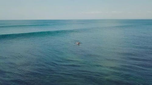Aerial Shot Over Surfer Paddling and Riding the Big Barrel of Waves in the Ocean