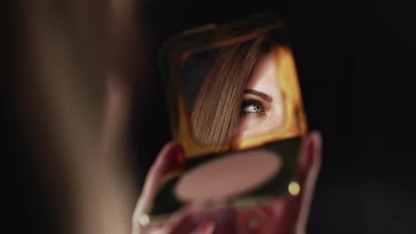 Reflection in Mirror of Womans Eyes with Shinning Makeup