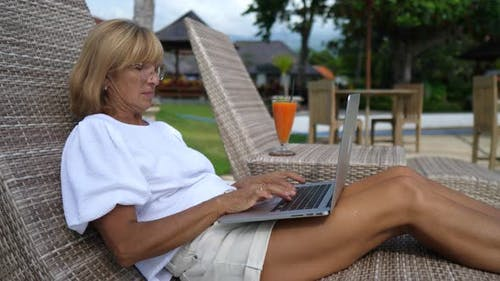 Middle Aged Caucasian Woman Works on Her Computer on a Sunbed By the Swimming Pool