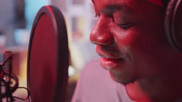 Close-Up of Afro-American Rapper Recording Song in Studio with Neon Light
