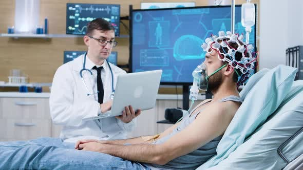 Doctor Using His Laptop in Modern Facility for Brain Analysis