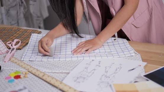 Fashion designer measuring fabric according to the pattern