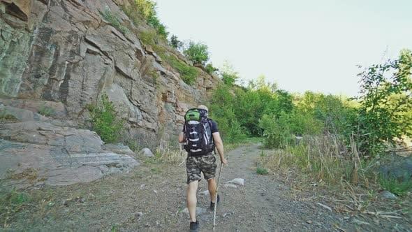 Reisender mit Rücken geht am Sommertag mit einem Stock in der Hand in der Nähe der Felsen auf dem Weg