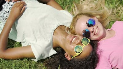 Two Female Friends Lying on Grass, Gossiping About Guys and Smiling, Friendship