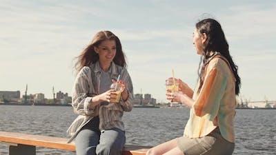 Girlfriends Sitting on Waterfront