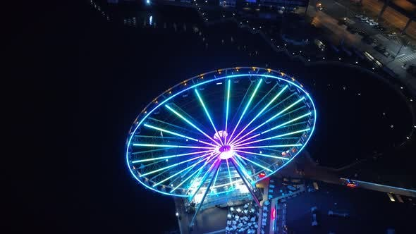 Helicopter View Passing Over Bright Ferris Wheel at Night
